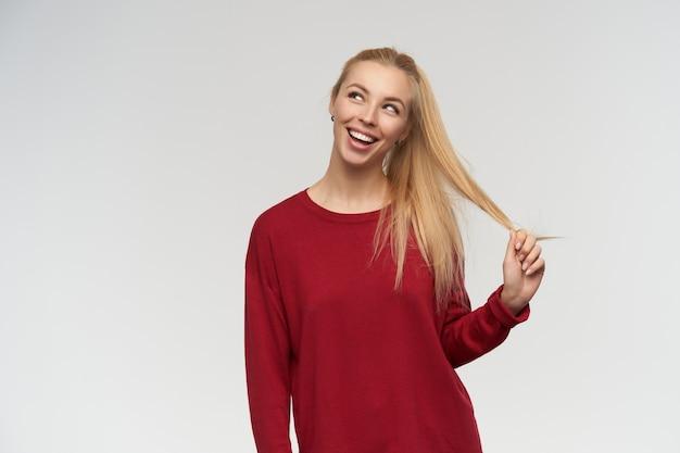 Porträt des attraktiven, erwachsenen mädchens mit den blonden langen haaren. trage einen roten pullover. menschen- und emotionskonzept. beobachten sie links im kopierraum, isoliert über weißem hintergrund
