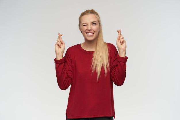 Porträt des attraktiven, erwachsenen mädchens mit den blonden langen haaren. trage einen roten pullover. menschen- und emotionskonzept. sie schaut auf den kopierplatz, isoliert über der weißen wand, drückt die daumen und betet