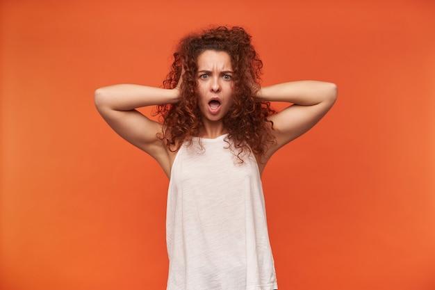 Porträt des attraktiven, erwachsenen rothaarigen mädchens mit dem lockigen haar. tragen einer weißen schulterfreien bluse. sie bedeckte ihre ohren mit den händen. schock im gesicht. isoliert über orange wand