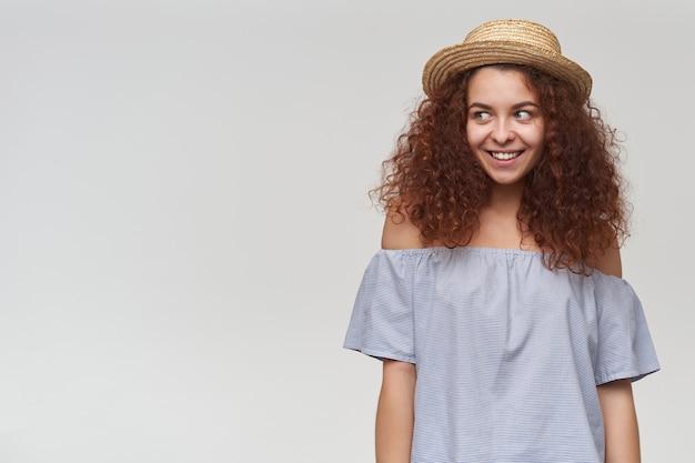 Porträt des attraktiven, erwachsenen rothaarigen mädchens mit dem lockigen haar. tragen sie eine gestreifte schulterfreie bluse und einen hut. flirty lächelnd. beobachten sie links den kopierbereich, isoliert über der weißen wand