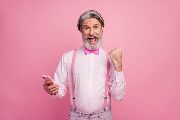 Porträt des attraktiven fröhlichen grauhaarigen mannes unter verwendung der zelle, die erfolg feiert
