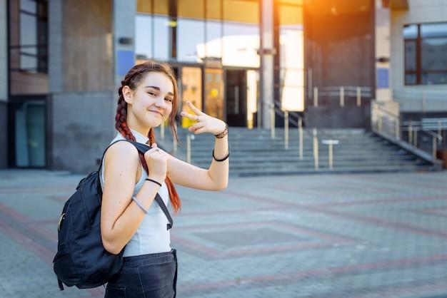 Porträt des attraktiven fröhlichen teenager-mädchens im weißen t-shirt mit schwarzem rucksack auf ihrer schulter. stilvoller schüler macht gesten mit seinen händen