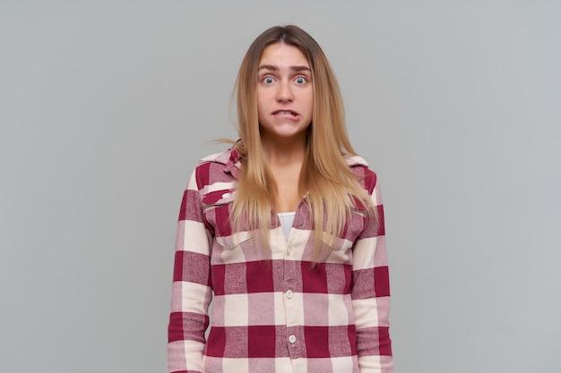 Porträt des attraktiven, geschockten mädchens mit den blonden langen haaren. tragen eines rot karierten hemdes. menschen- und emotionskonzept. vor stress auf die lippe beißen. isoliert über graue wand