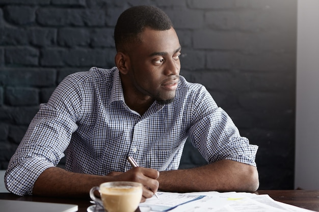 Porträt des attraktiven jungen afroamerikanischen ceo im hemd, der einige papiere durchläuft