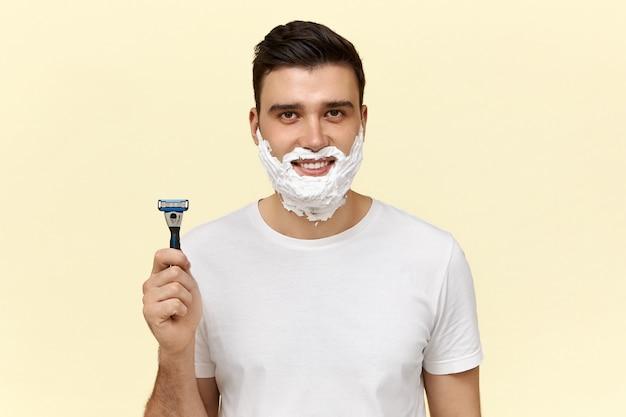 Porträt des attraktiven jungen dunkelhaarigen kerls im lässigen t-shirt, das mit rasierschaum auf seinem gesicht aufwirft und einwegrasierer hält