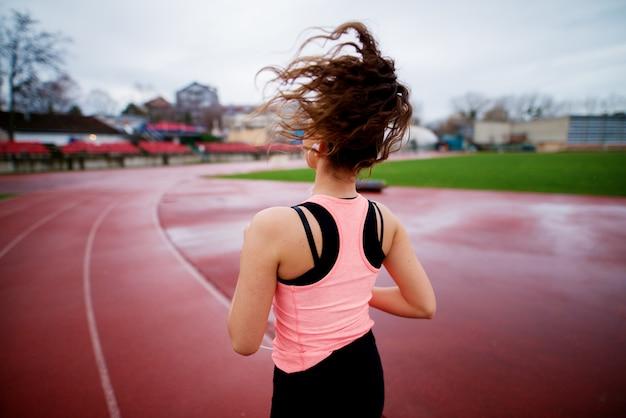 Porträt des attraktiven jungen glücklichen fitnessmädchens, das beim musikhören draußen auf der laufbahn joggt.