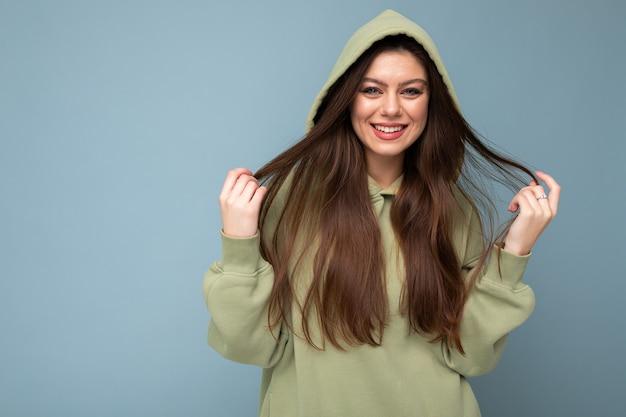 Porträt des attraktiven jungen kaukasischen lächelnden brunettefrauenmodells im modischen khakifarbenen hoodie und