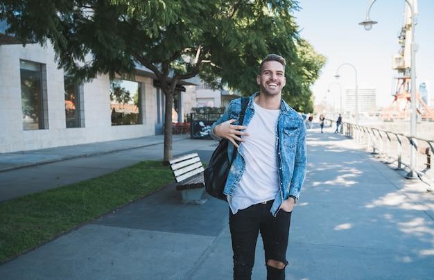 Porträt des attraktiven jungen mannes, der auf der straße mit rucksack auf seinen schultern geht. stadtkonzept.