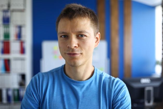 Porträt des attraktiven jungen mannes, der blaues hemd trägt. kluger mann, der im büro sitzt. kreativer innenarchitekt oder geschäftsmann.