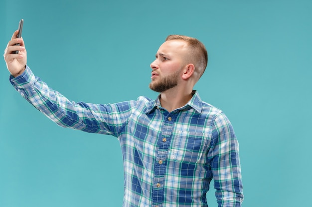 Porträt des attraktiven jungen mannes, der ein selfie mit seinem smartphone nimmt. auf blauem raum isoliert.