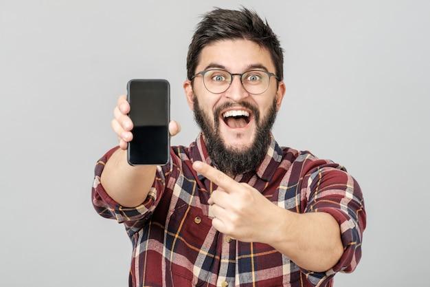 Porträt des attraktiven jungen mannes, der smartphone für werbung präsentiert