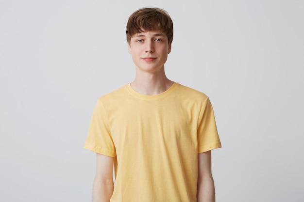Porträt des attraktiven jungen mannes mit kurzem haarschnitt trägt gelbes t-shirt