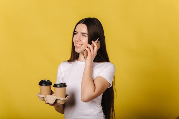 Porträt des attraktiven mädchens, das am telefon spricht und tasse kaffee hält