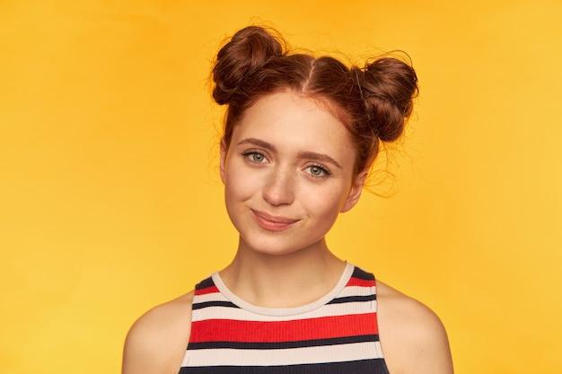 Porträt des attraktiven mädchens des roten haares mit zwei brötchen und gesunder haut. tragen eines gestreiften hemdes und beobachten mit niedlichem lächeln, nahaufnahme, stehen isoliert über gelber wand