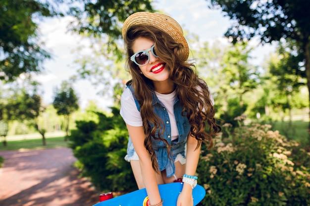 Porträt des attraktiven mädchens mit dem langen lockigen haar im hut, das mit skateboard im sommerpark aufwirft. sie trägt jeanswams und eine sonnenbrille. sie lächelt.
