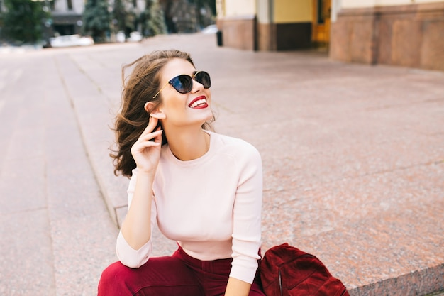 Porträt des attraktiven mädchens mit schneeweißem lächeln und weinigen lippen, die auf treppen in der stadt sitzen. sie trägt eine sonnenbrille und weinige kleidung.