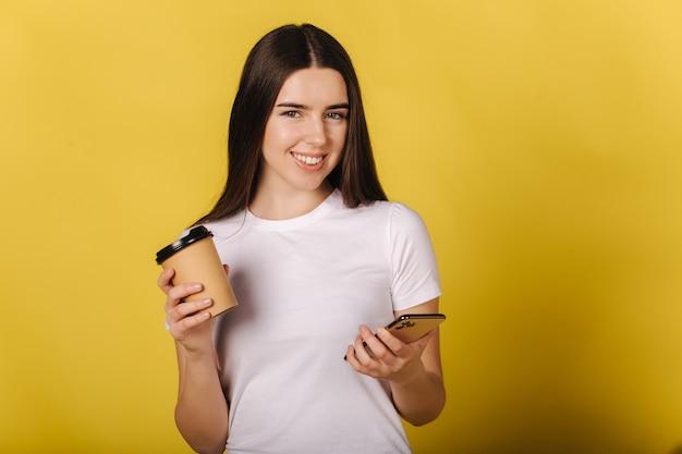 Porträt des attraktiven mädchens unter verwendung des telefons und halten tasse kaffee