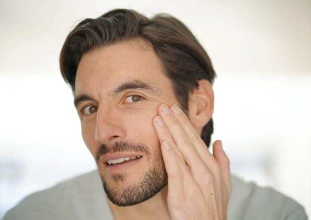 Porträt des attraktiven mannes falten überprüfend, kamera betrachtend