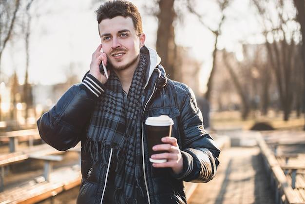 Porträt des attraktiven mannes im tragen der jacke unter verwendung des mobiltelefons und des haltens des kaffee zum mitnehmen