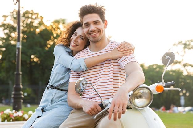 Porträt des attraktiven paares, lächelnd und zusammen umarmend, während auf motorrad im stadtpark sitzend