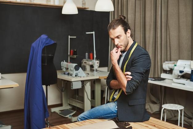 Porträt des attraktiven reifen konzentrierten modedesigners, der in seiner werkstatt sitzt, beiseite schaut, kinn mit der hand hält und über das thema der nächsten kleidungskollektion nachdenkt