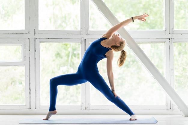 Porträt des attraktiven sportlichen übenden yoga der jungen frau innen