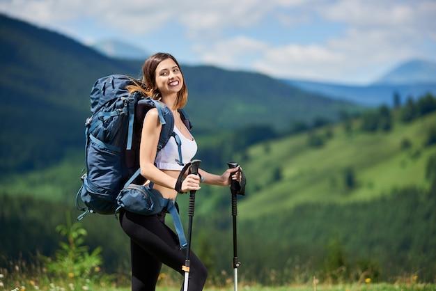 Porträt des attraktiven sportlichen weiblichen wanderers mit blauem rucksack und den wanderstöcken, lächelnd auf die oberseite eines hügels und genießen sommertag. berge, wälder und bewölkter himmel auf dem unscharfen hintergrund