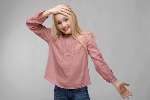 Porträt des attraktiven süßen entzückenden blonden jugendlichmädchens in der rosa bluse