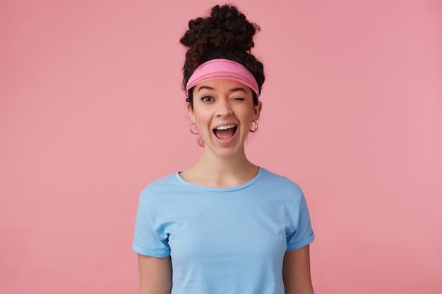 Porträt des attraktiven, verspielten mädchens mit dunklem lockigem haarknoten. trägt rosa visier, ohrringe und blaues t-shirt. hat sich geschminkt. emotionskonzept