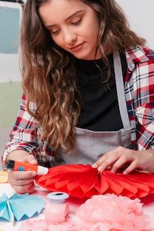 Porträt des attraktiven weiblichen künstlers, der rote origamiblume haftet