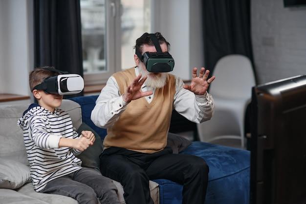 Porträt des aufgeregten älteren mannes, der vr-brille benutzt, die zu hause auf sofa mit lachendem enkel neben ihm sitzt