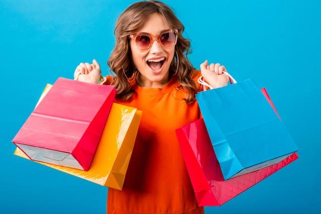 Porträt des aufgeregten attraktiven lächelnden stilvollen frauen-shopaholic im orangefarbenen trendigen kleid, das einkaufstaschen auf blauem studiohintergrund lokalisiert hält