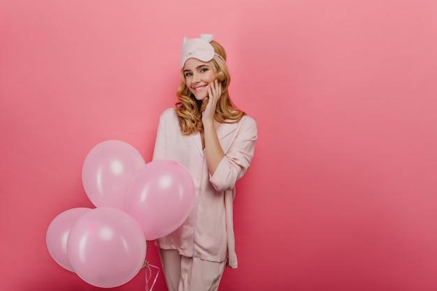 Porträt des aufgeregten geburtstagskindes, das auf geschenke wartet. foto des interessierten weiblichen modells im schlafanzug, der bündel der rosa luftballons hält.