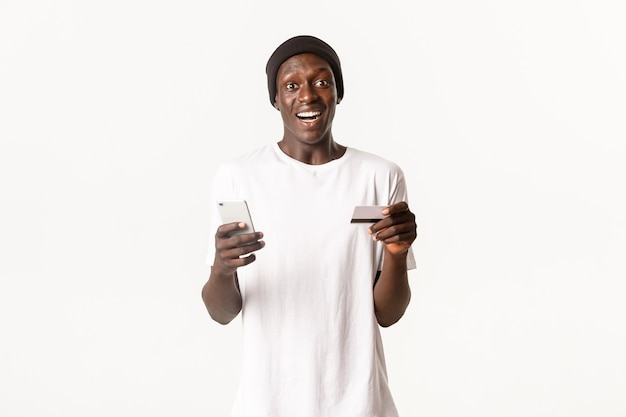 Porträt des aufgeregten, glücklichen afroamerikanischen jungen männlichen studenten, der kreditkarte und smartphone mit amüsiertem lächeln hält