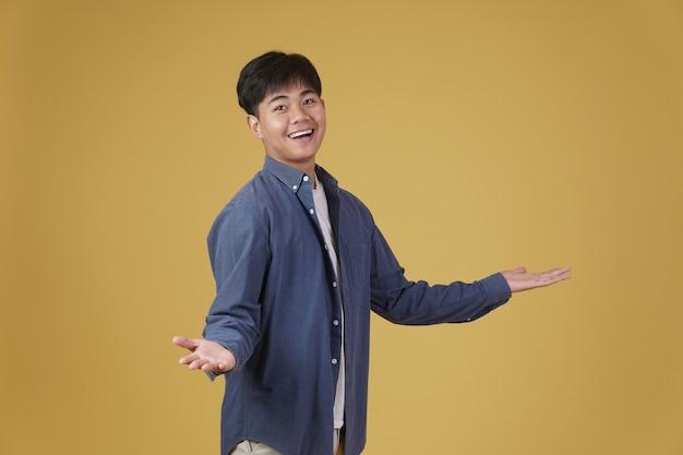Porträt des aufgeregten glücklichen gutaussehenden jungen asiatischen mannes, der beiläufig lächelnd mit offener handgeste isoliert gekleidet gekleidet ist