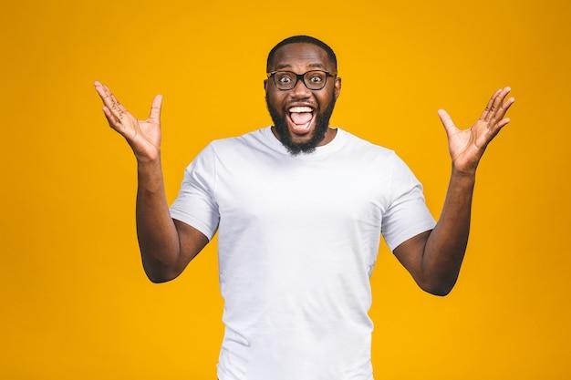 Porträt des aufgeregten jungen afroamerikanischen mannes, der in schock und erstaunen schreit. der überraschte mann, der beeindruckt aussieht, kann sein eigenes glück und seinen erfolg nicht fassen
