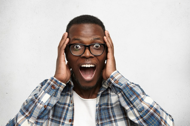 Porträt des aufgeregten jungen afroamerikanischen mannes, der in schock und erstaunen schreit, die hände auf kopf halten. überrascht sieht der bug-eyed schwarze hipster beeindruckt aus, kann sein eigenes glück und seinen erfolg nicht fassen
