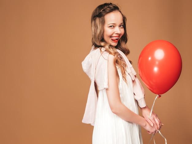 Porträt des aufgeregten jungen mädchens, das im weißen kleid des modischen sommers aufwirft. lächelnde frau mit der roten ballonaufstellung. modell bereit für die party, zeigt ihre zunge