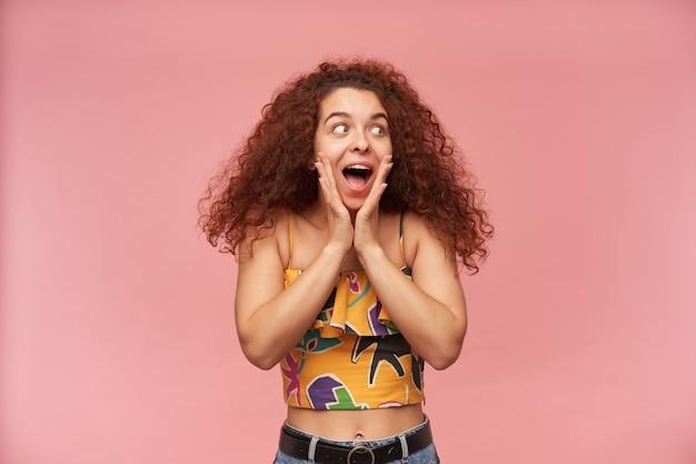 Porträt des aufgeregten, rothaarigen mädchens mit dem lockigen haar, das bunte schulterfreie bluse trägt