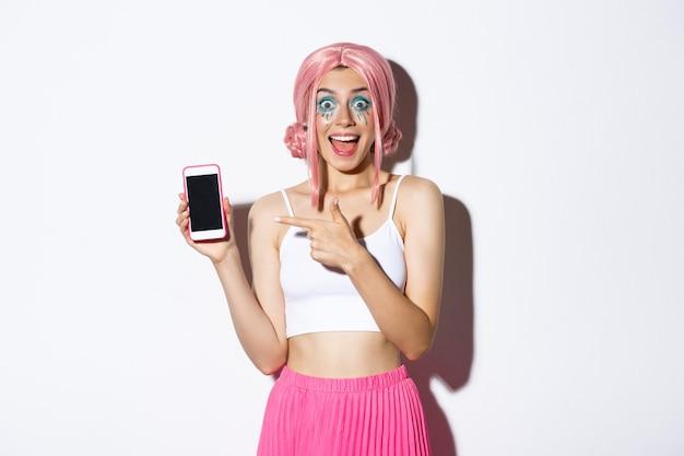 Porträt des aufgeregten schönen mädchens in halloween-kostüm, rosa perücke und hellem make-up, zeigefinger auf handy mit erstauntem gesicht, stehend.