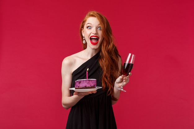 Porträt des aufgeregten und amüsierten glücklichen rothaarigen b-tagesmädchens, das kuchen mit brennender kerze hält und versucht, wunsch zu blasen, damit traum für wahr wird, auf party trinkend wein auf einer roten wand feiert