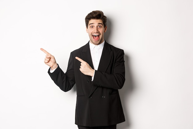 Porträt des aufgeregten und glücklichen mannes im anzug, der werbung zeigt