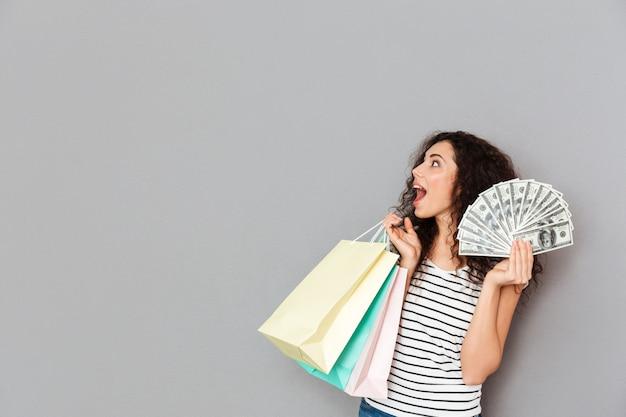 Porträt des aufgeregten weiblichen shopaholic, der mit vielen paketen und fan von dollarscheinen in den händen betrachten etwas interessanten kopienraum steht
