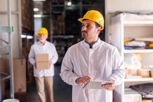 Porträt des aufsehers in der weißen uniform und im helm auf kopf, der tablette hält und regale beim stehen in der lebensmittelfabrik betrachtet.