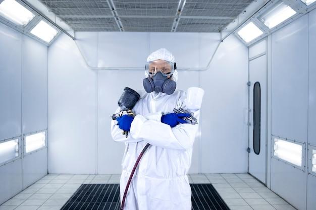 Porträt des autolackierers, der in der farbkammerwerkstatt steht und malpistole hält.