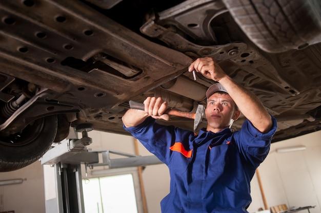 Porträt des automechanikers arbeitend mit werkzeugen unter auto