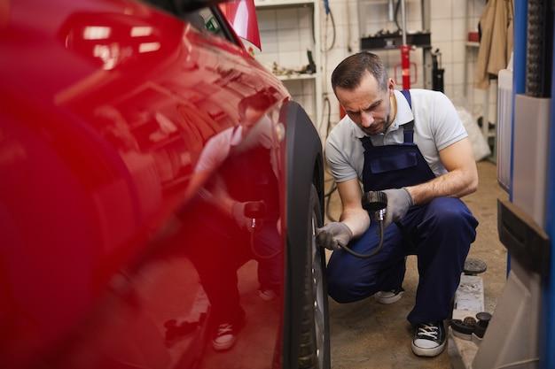 Porträt des automechanikers, der den druck in den reifen während der fahrzeuginspektion im garagengeschäft prüft, kopienraum