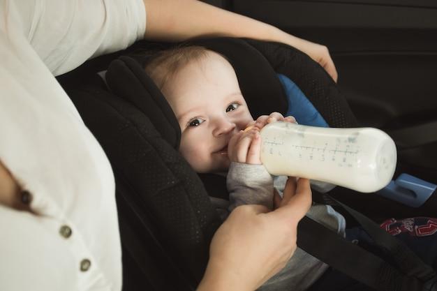 Porträt des babys, das milch aus der flasche auf dem rücksitz des autos trinkt