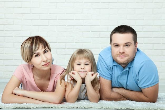 Porträt des babys und ihrer eltern, die auf teppich im wohnzimmer liegen