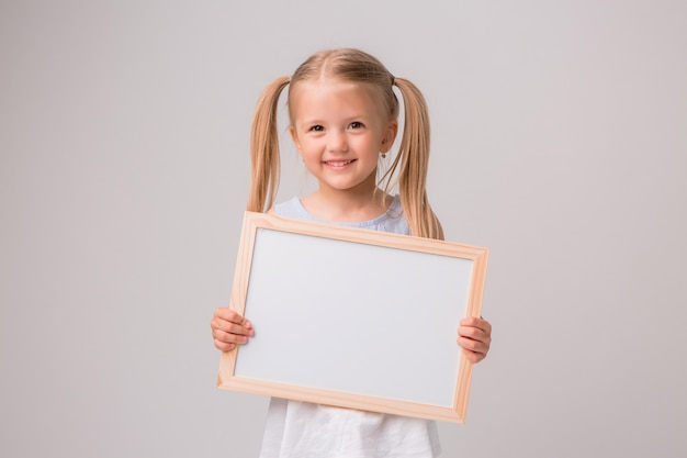 Porträt des babys weißes reißbrett auf weißem hintergrund halten